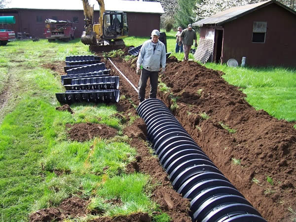 A pressure distribution lateral being installed using graveless chambers in three foot wide trenches.